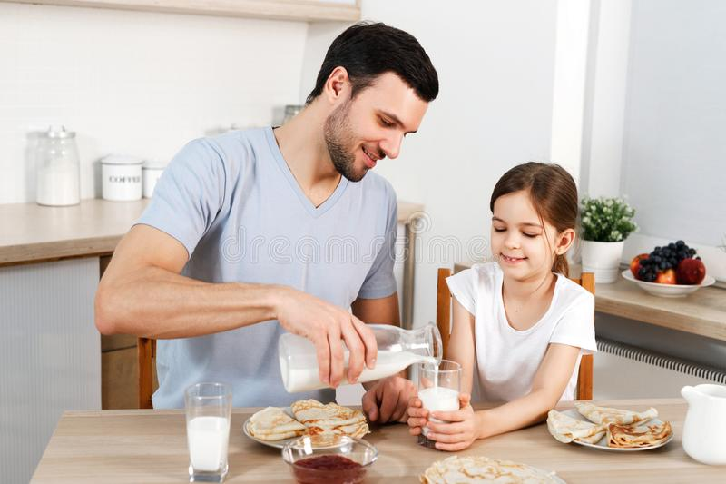 Den lyckliga fadern och dottern har frukosten på kök, äter läckra pannkakor med driftstopp, drink mjölkar, tycker om läcker mat royaltyfria foton