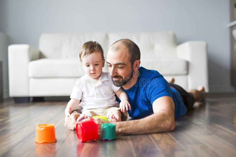 Den lyckliga fadern och lilla sonen som spelar med leksaken, blockerar hemma fotografering för bildbyråer