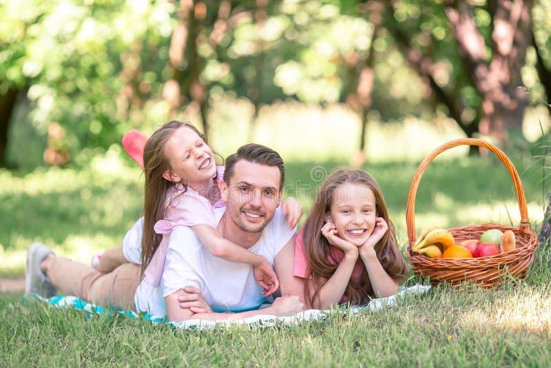 Den lyckliga fadern och sm? daughers kopplar av vid sj?n fotografering för bildbyråer