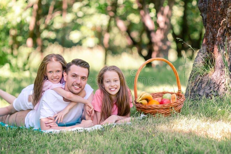 Den lyckliga fadern och sm? daughers kopplar av vid sj?n arkivbilder