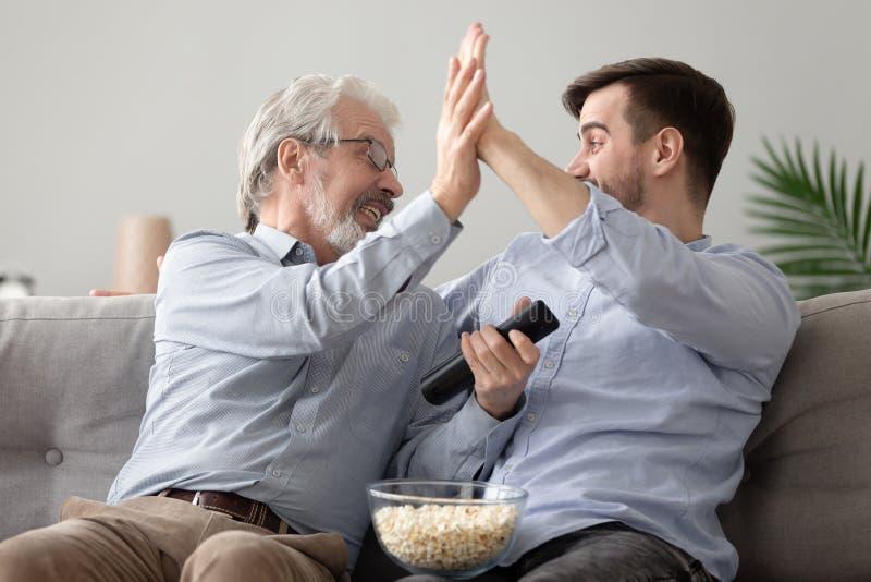 Den lyckliga fadern och sonen firar laget f?r att segra hemma royaltyfri fotografi