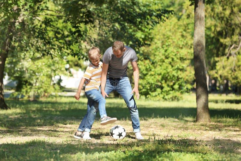 Den lyckliga fadern och sonen som spelar fotboll parkerar in royaltyfri foto