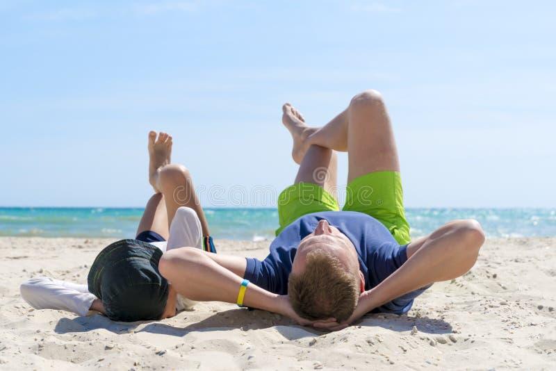 Den lyckliga fadern och sonen spenderar tid tillsammans på stranden Faderskapfamiljbegrepp dagen avlar lyckligt arkivbild