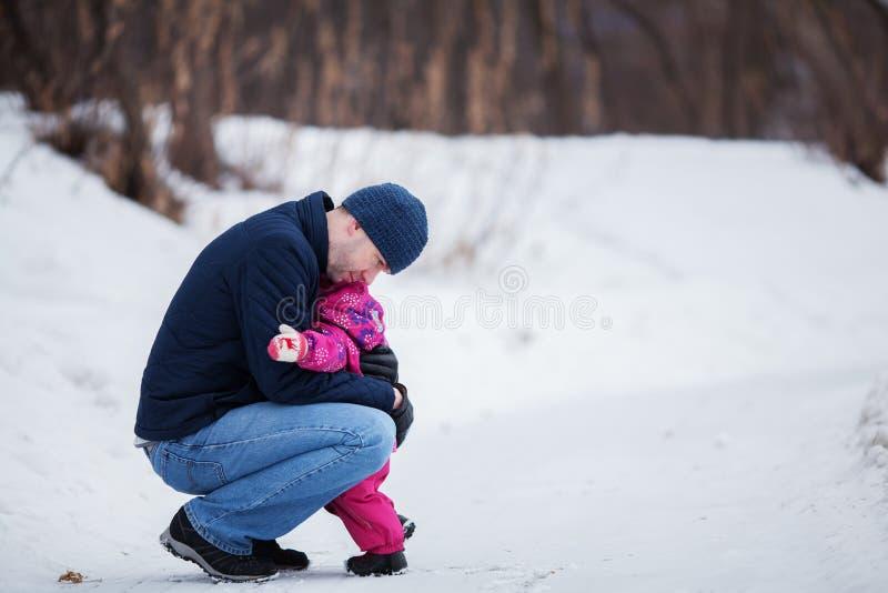 Den lyckliga fadern som går med den nätta härliga lilla flickan i vinter, parkerar royaltyfria foton