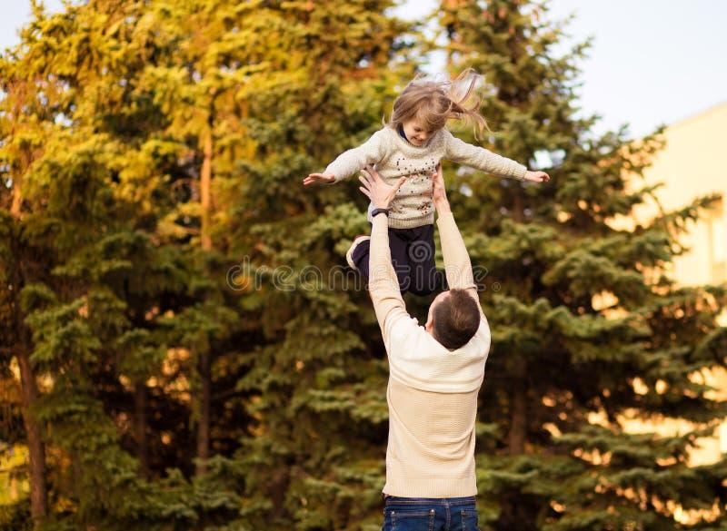Den lyckliga fadern som har roligt, kastar upp i luftbarn dagfader s Familj f?r enkel f?r?lder arkivbild