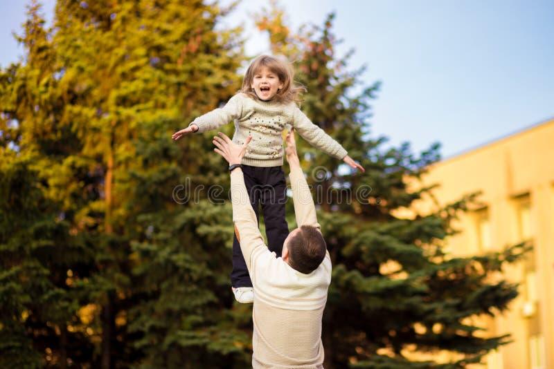 Den lyckliga fadern som har roligt, kastar upp i luftbarn dagfader s Familj f?r enkel f?r?lder arkivfoto
