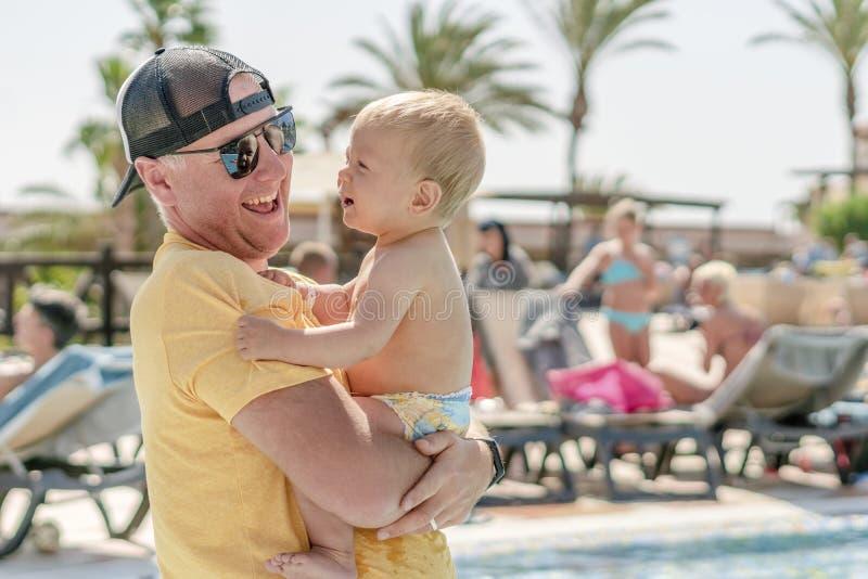 Den lyckliga fadern som spenderar tid med hans, behandla som ett barn sonen vid pölen i semesterorten fotografering för bildbyråer