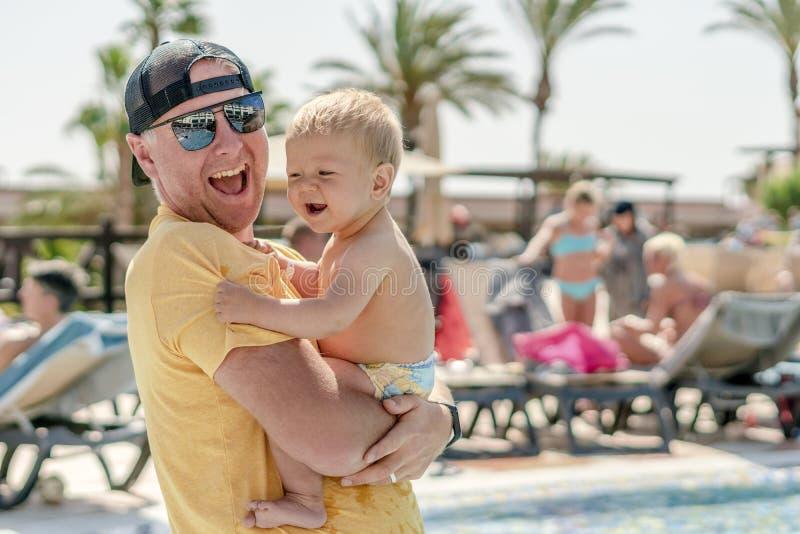 Den lyckliga fadern som spenderar tid med hans, behandla som ett barn sonen vid pölen i semesterorten arkivfoton