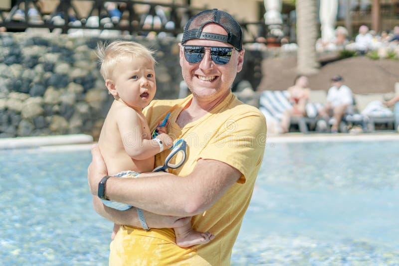 Den lyckliga fadern som spenderar tid med hans, behandla som ett barn sonen vid p?len i semesterorten royaltyfri bild