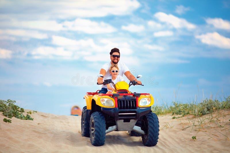 Den lyckliga familj-, fader- och sonridningen på atvkvadrat cyklar på den sandiga stranden royaltyfri fotografi
