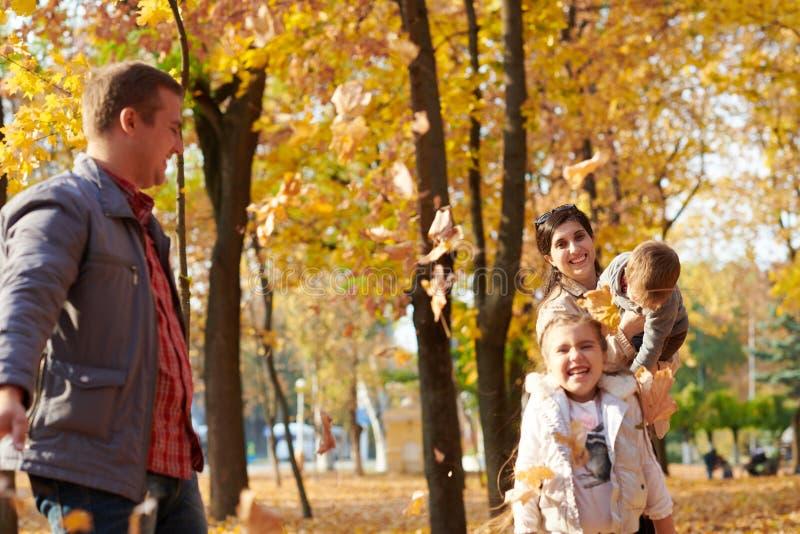Den lyckliga familjen är i höststad parkerar Barn och föräldrar Dem som poserar, ler, spelar och har gyckel Ljusa gula träd royaltyfri fotografi