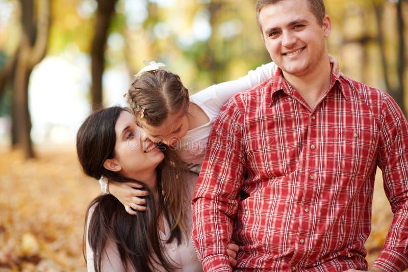 Den lyckliga familjen är i höststad parkerar Barn och föräldrar Dem som poserar, ler, spelar och har gyckel Ljusa gula träd arkivbild