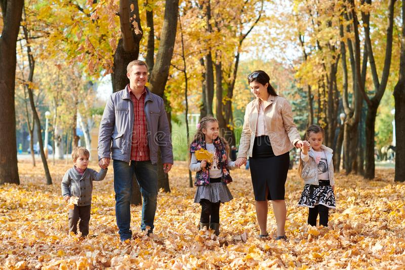 Den lyckliga familjen är i höststad parkerar Barn och föräldrar Dem som poserar, ler, spelar och har gyckel Ljusa gula träd arkivfoton