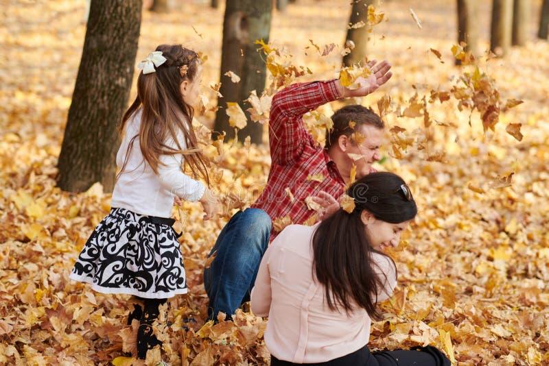 Den lyckliga familjen är i höststad parkerar Barn och föräldrar Dem som poserar, ler, spelar och har gyckel Ljusa gula träd arkivbilder