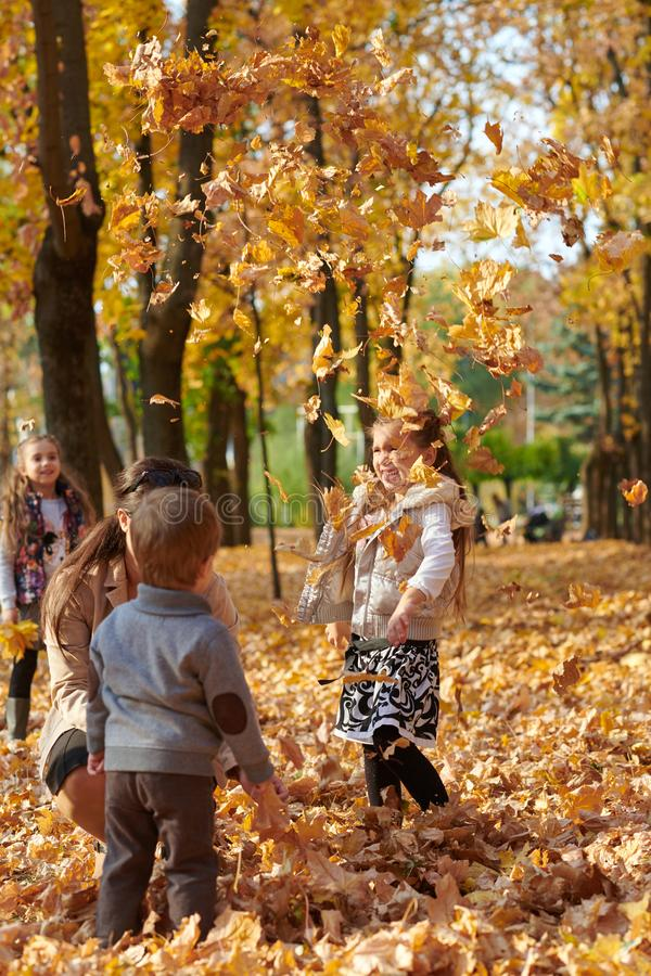 Den lyckliga familjen är i höststad parkerar Barn och föräldrar Dem som poserar, ler, spelar och har gyckel Ljusa gula träd royaltyfria foton