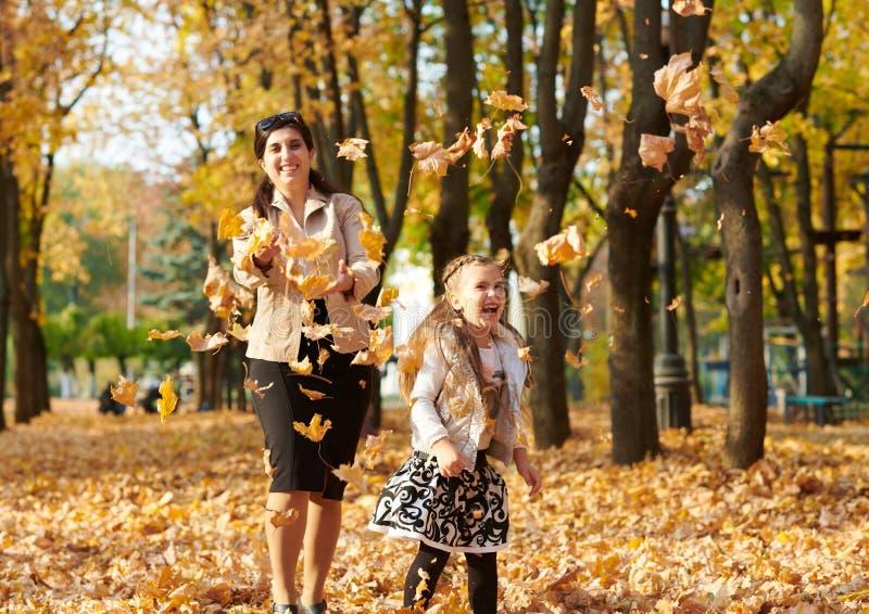 Den lyckliga familjen är i höststad parkerar Barn och föräldrar Dem som poserar, ler, spelar och har gyckel Ljusa gula träd royaltyfri foto