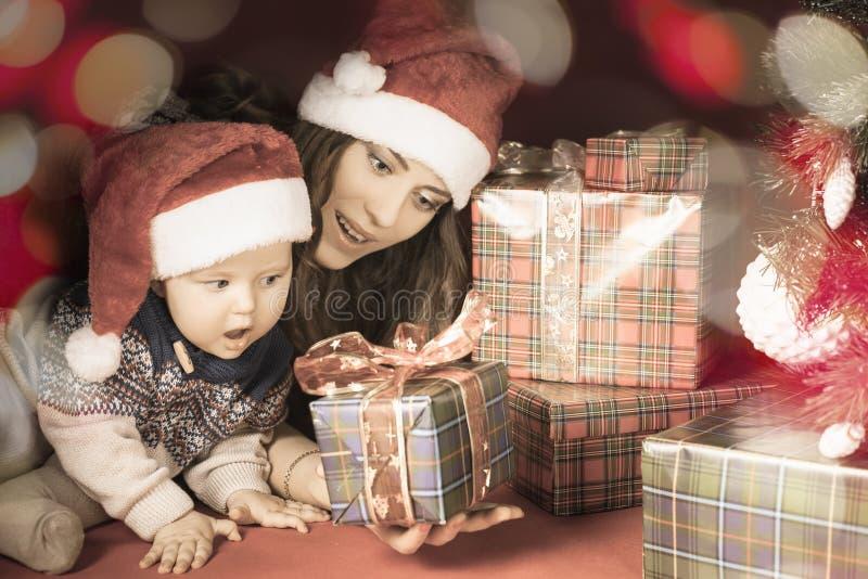 Den lyckliga familjen av behandla som ett barn och fostrar nära julgranen royaltyfri bild