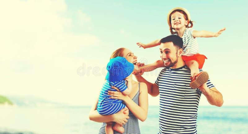 Den lyckliga familjen av fadern, modern och två barn, behandla som ett barn sonen och da royaltyfria foton