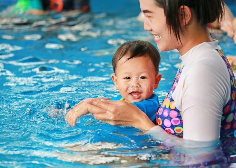 Den lyckliga familjen av mammaundervisning behandla som ett barn pojken i simbassäng royaltyfri bild