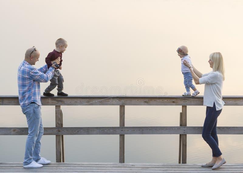 Den lyckliga familjen av två föräldrar och barn, pojkar en, behandla som ett barn flickan, har bra tid på flodbryggan Solnedgång fotografering för bildbyråer