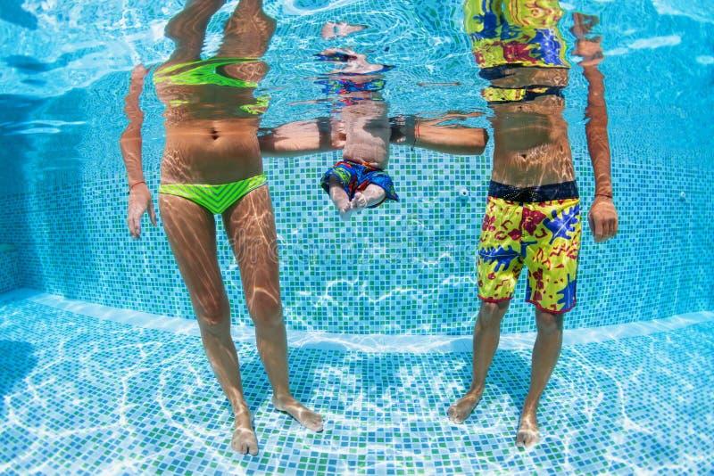 Den lyckliga familjen - avla, fostra med behandla som ett barn i simbassäng royaltyfri bild