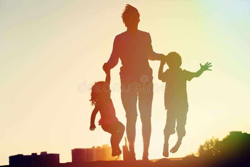 Den lyckliga familjen - avla med ungar som hoppar från glädje på solnedgången arkivfoton