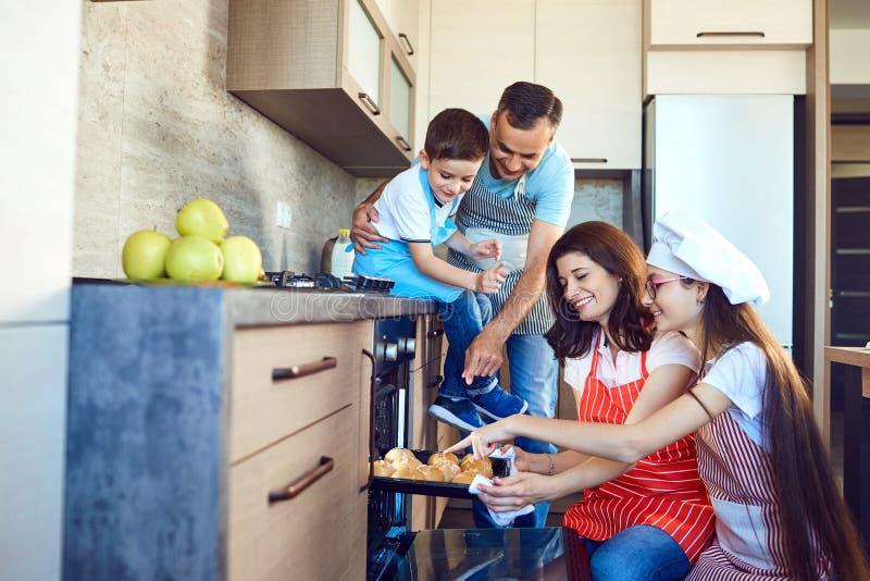 Den lyckliga familjen bakar bullar i ugnen i köket arkivfoto