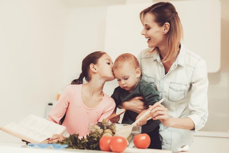 Den lyckliga familjen förbereder en sallad på kök arkivbild