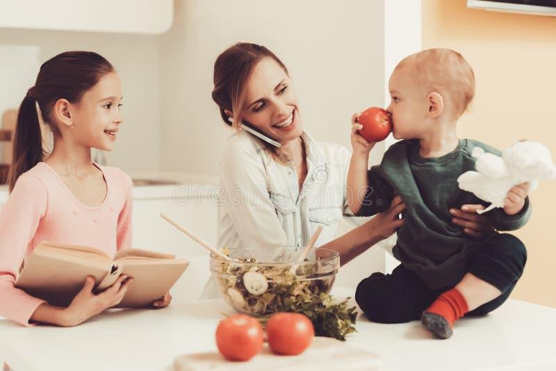 Den lyckliga familjen förbereder en sallad på kök arkivfoto