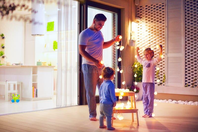 Den lyckliga familjen, fader med söner dekorerar öppet utrymmeuteplatsområde med julgirlander arkivbild