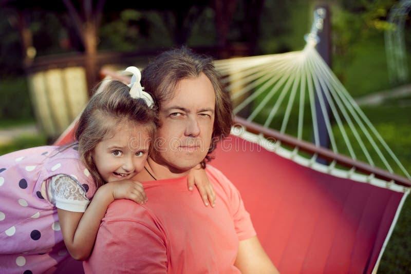 Den lyckliga familjen, fadern och dottern kopplar av i sommaren utomhus I arkivfoto