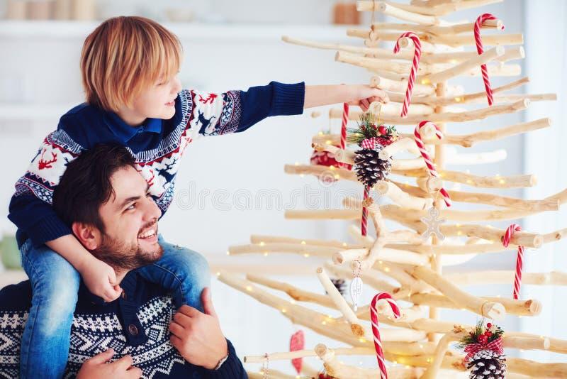 Den lyckliga familjen, fadern och sonen dekorerar handcrafted det hemmastadda julträdet som göras av drivved royaltyfria foton