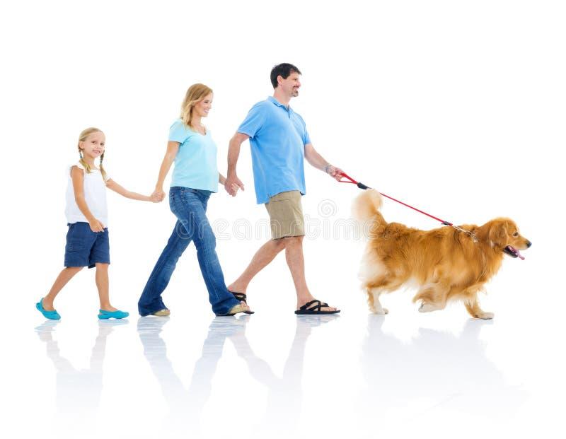 Den lyckliga familjen går hunden arkivbild