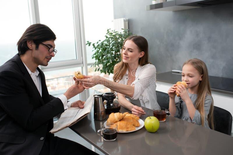 Den lyckliga familjen har en frukost hemma fotografering för bildbyråer