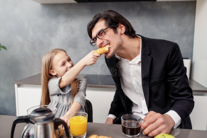 Den lyckliga familjen har en frukost hemma royaltyfri bild
