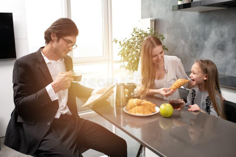 Den lyckliga familjen har en frukost hemma royaltyfria bilder