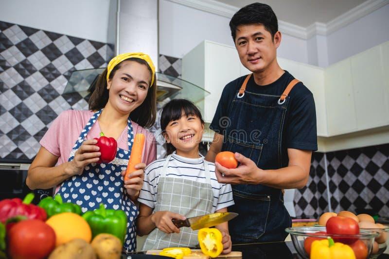 Den lyckliga familjen har farsan, mamman och deras lilla dotter som tillsammans lagar mat i k?ket royaltyfri bild