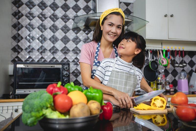 Den lyckliga familjen har farsan, mamman och deras lilla dotter som tillsammans lagar mat i k?ket royaltyfri foto