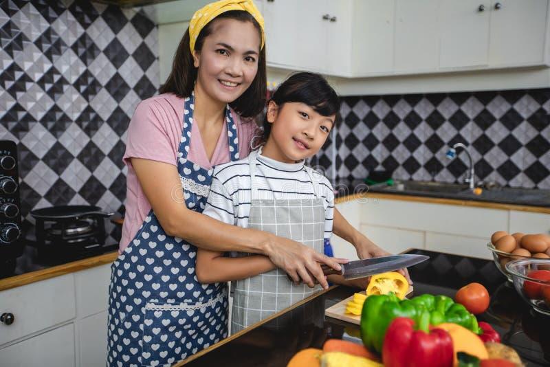 Den lyckliga familjen har farsan, mamman och deras lilla dotter som tillsammans lagar mat i k?ket fotografering för bildbyråer