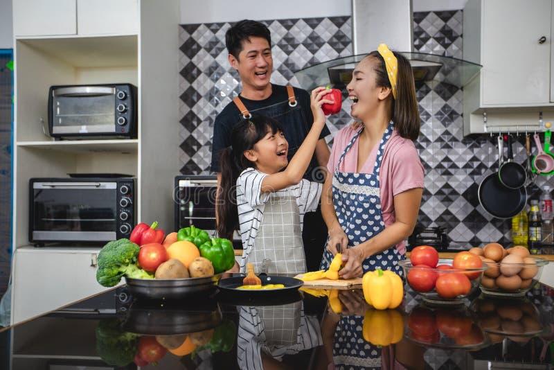 Den lyckliga familjen har farsan, mamman och deras lilla dotter som tillsammans lagar mat i k?ket arkivbild
