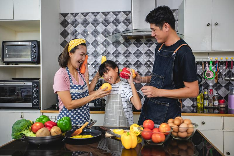 Den lyckliga familjen har farsan, mamman och deras lilla dotter som tillsammans lagar mat i k?ket royaltyfri fotografi