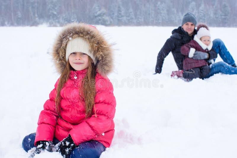 Den lyckliga familjen har gyckel i snöig dag för vinter royaltyfria bilder
