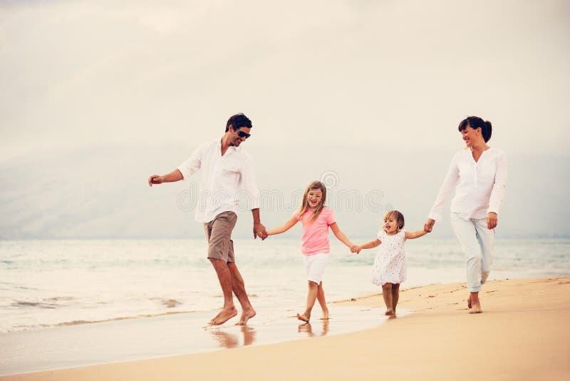 Den lyckliga familjen har gyckel som går på stranden på solnedgången arkivfoto