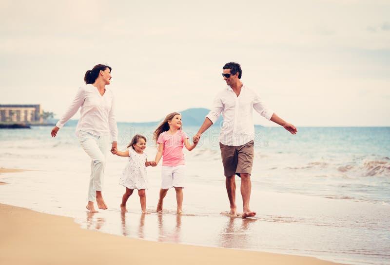 Den lyckliga familjen har gyckel som går på stranden på solnedgången royaltyfri foto