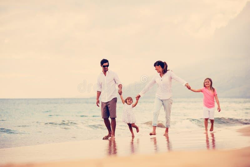 Den lyckliga familjen har gyckel som går på stranden på solnedgången royaltyfria bilder