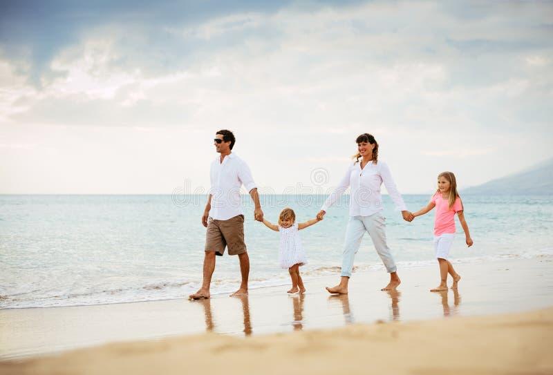 Den lyckliga familjen har gyckel som går på stranden på solnedgången arkivbild