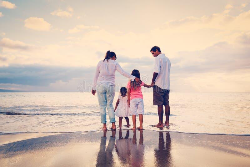 Den lyckliga familjen har gyckel som går på stranden på solnedgången arkivfoton