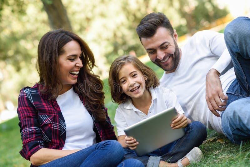 Den lyckliga familjen i ett stads- parkerar att spela med minnestavladatoren arkivfoto