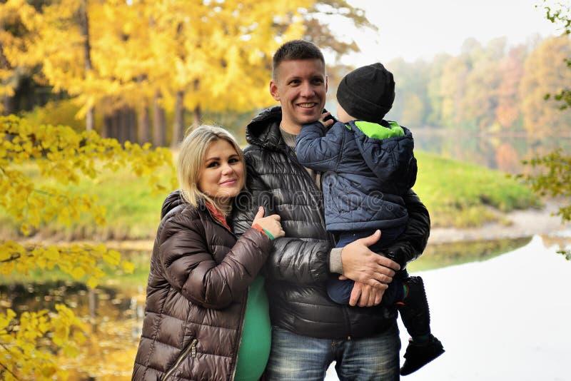 Den lyckliga familjen i höst parkerar nära sjön royaltyfri foto