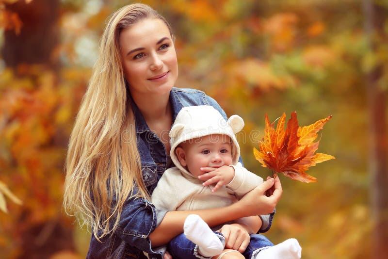 Den lyckliga familjen i hösten parkerar royaltyfri fotografi